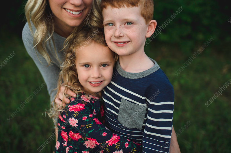 Portrait of girl, brother and mother hugging