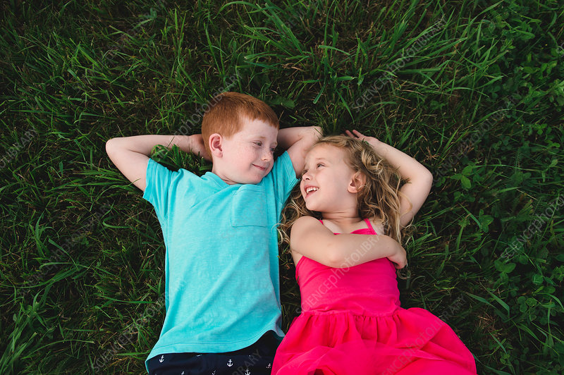 Boy and sister lying on grass looking at each other