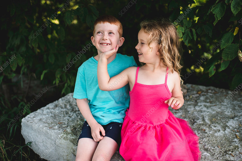 Girl with hand on brother's chin, sitting on rock