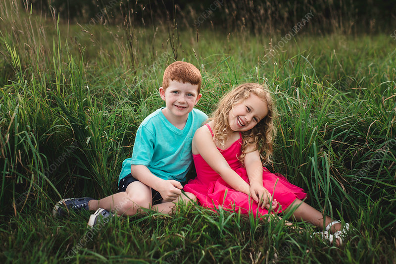 Portrait of girl and brother sitting in field