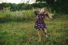 Blond haired girl running and pulling a face in field