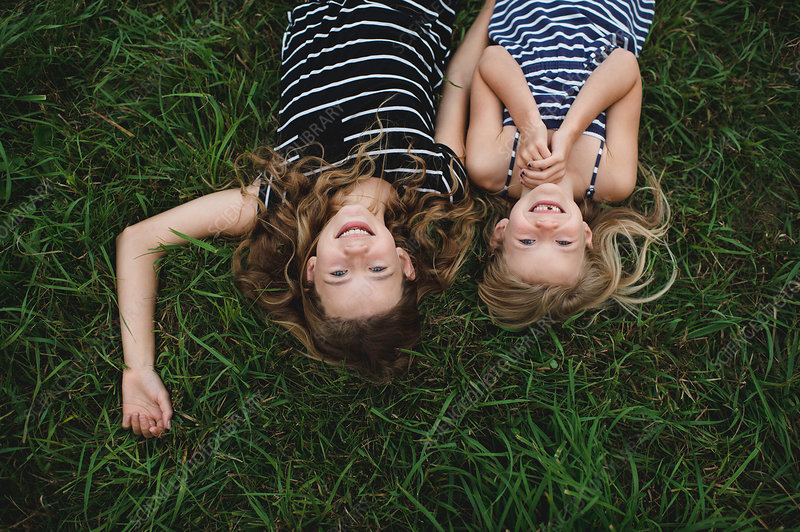 Upside down portrait of girl and her sister lying on grass