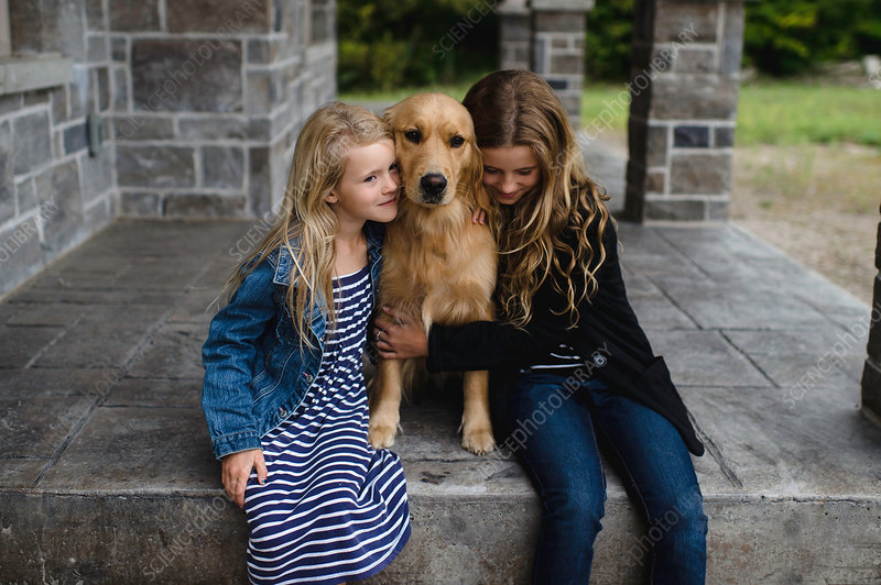 Girl and her sister sitting on patio hugging their dog