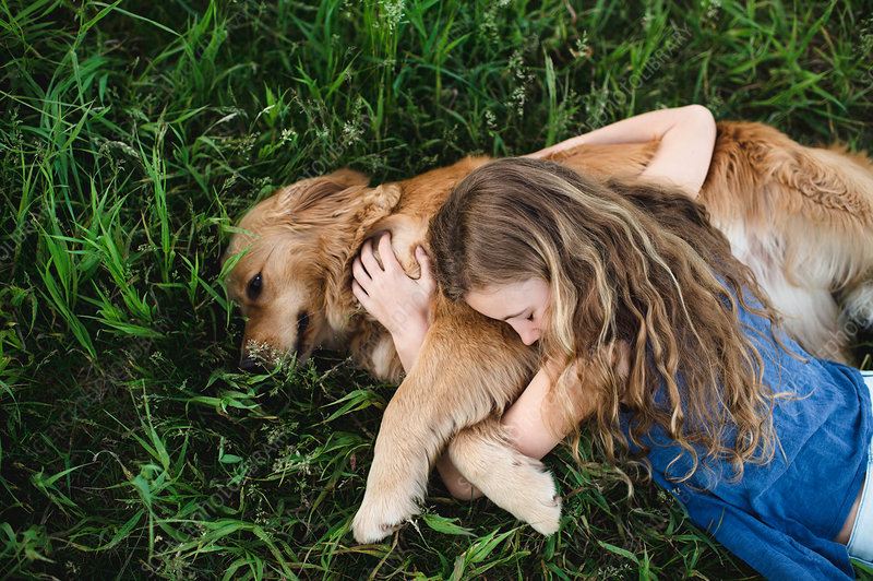 Overhead view of girl lying on grass hugging dog