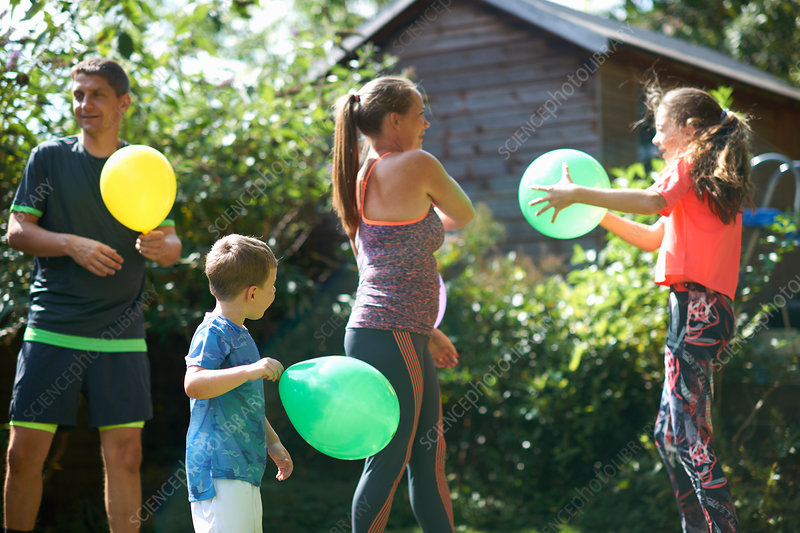 Family playing with balloons in garden