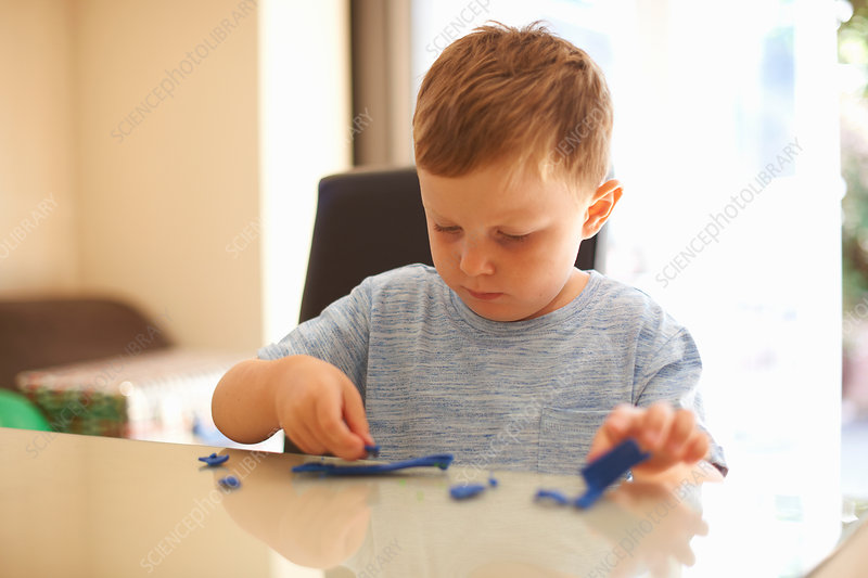 Young boy sitting at table, playing with modelling clay