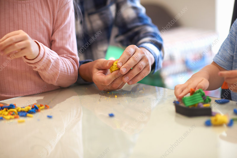 Father, son and daughter, playing with modelling clay
