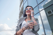 Businesswoman walking outdoors, using smartphone