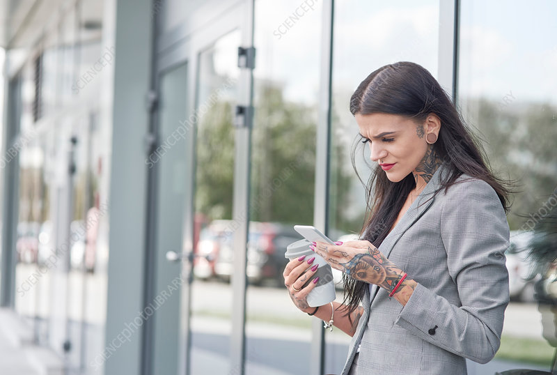 Businesswoman outdoors, holding coffee cup and smartphone