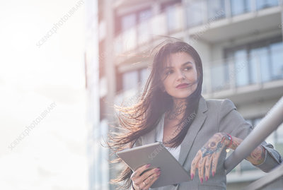 Businesswoman outdoors, holding digital tablet