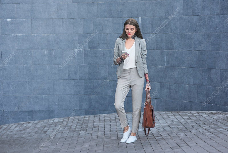 Businesswoman outdoors, using smartphone