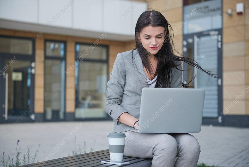 Businesswoman outdoors with laptop and coffee