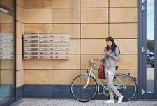Businesswoman walking bicycle, using smartphone