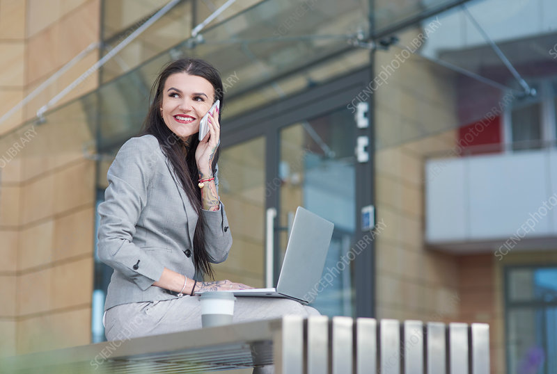 Businesswoman sitting outdoors, using laptop
