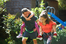 Family playing piggyback race in garden