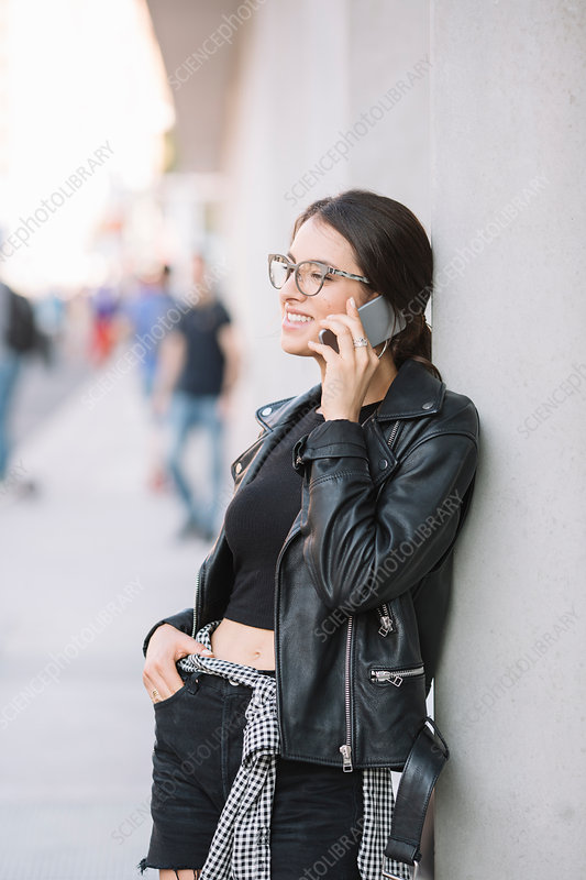 Woman leaning against wall using smartphone