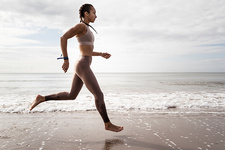 Side view of female runner running barefoot at beach