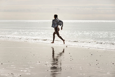 Young female runner running barefoot at beach