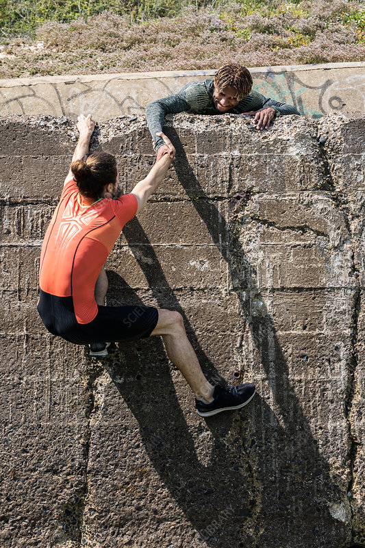 Young male free climber helping friend climb up