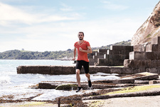 Young male runner running along water's edge of sea defence