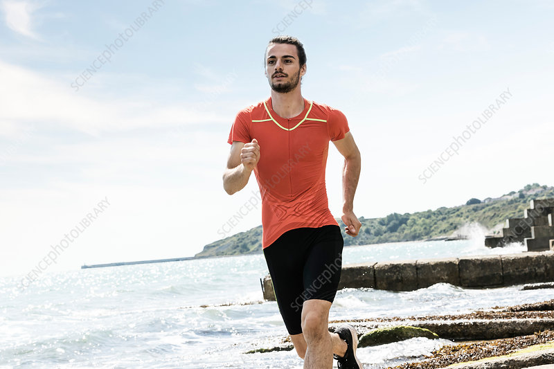Young male runner running along beach