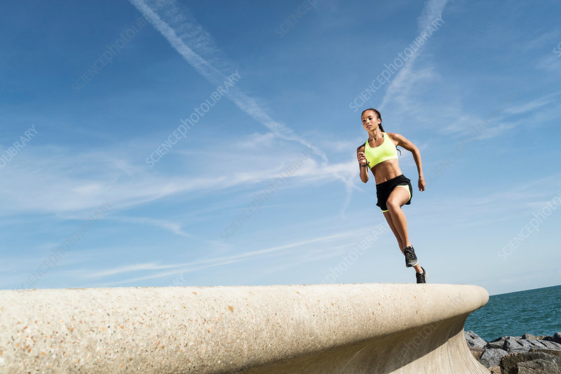 Low angle view of female runner running along sea wall