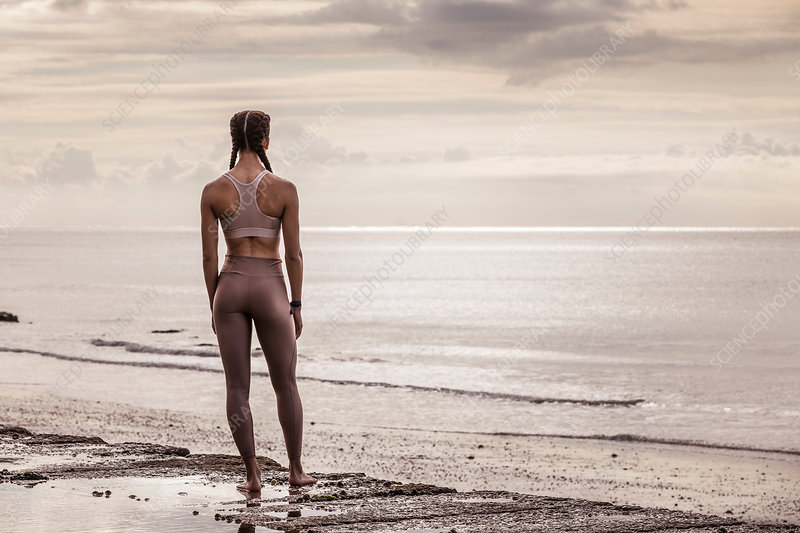 Rear view of female runner looking out to sea