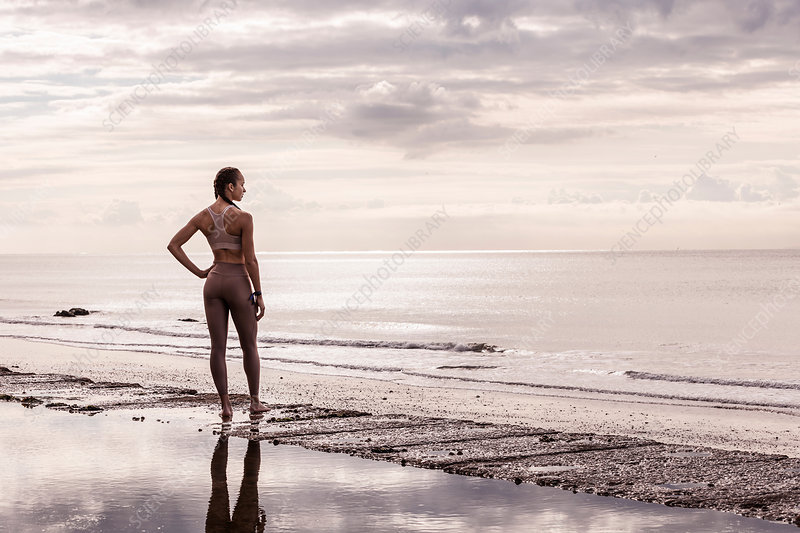 Young female runner at water's edge looking out to sea