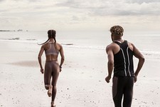 Rear view of young male and female runners running on beach