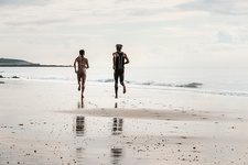 Male and female runners running barefoot along beach