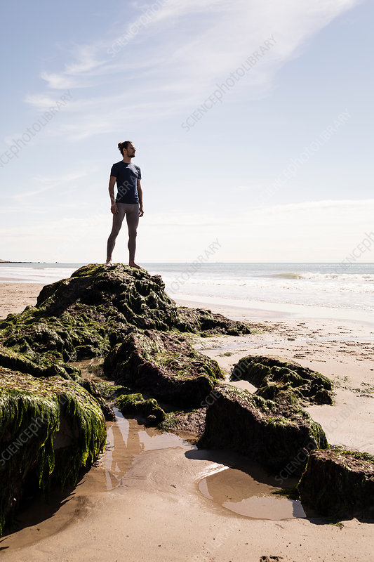 Young male runner looking out at sea from beach rock