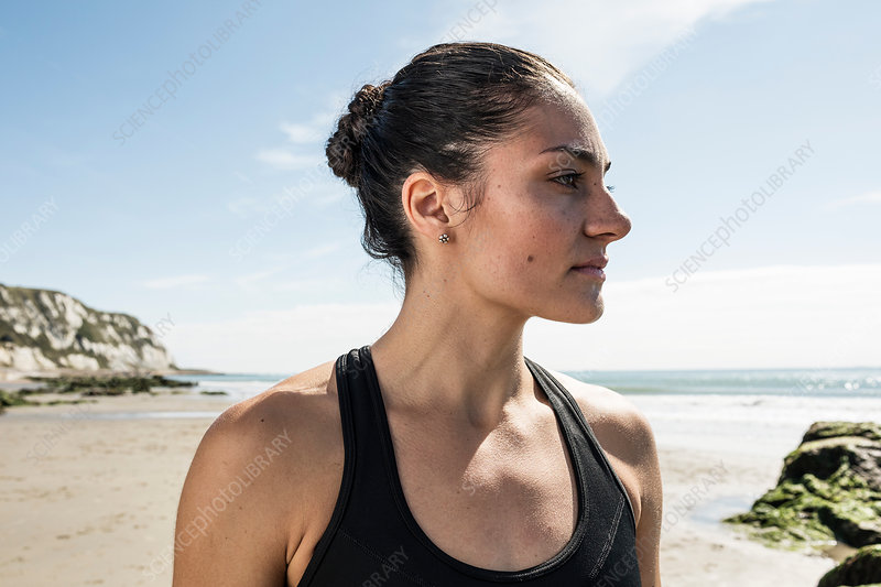 Young female runner gazing from beach