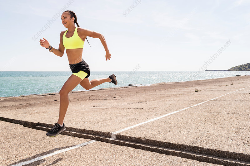 Young woman running outdoors, jumping over gap in bridge