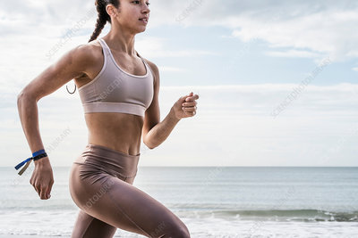 Young woman running along beach, close-up, mid section