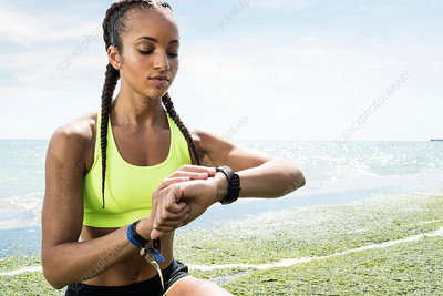 Young woman beside sea, looking at activity tracker
