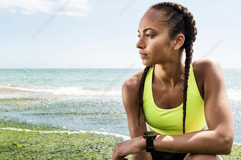 Young woman wearing sports clothing, crouching beside sea