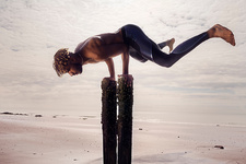 Young man balancing horizontally on wooden beach posts