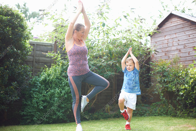 Mother and son exercising, standing in yoga position