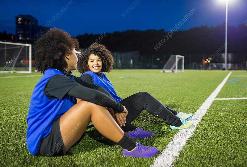 Female football players sitting by field, UK
