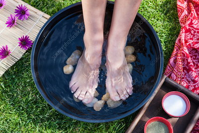 Woman's feet in foot bath, low section