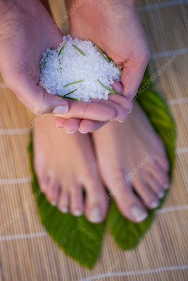 Woman standing on leaves, holding salt crystals