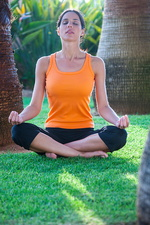 Woman sitting, meditating, outdoors