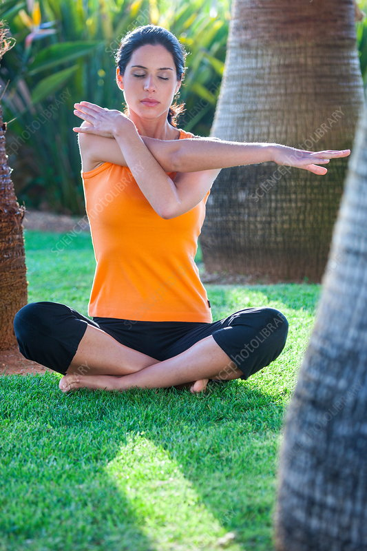 Woman sitting outdoors, stretching, meditating