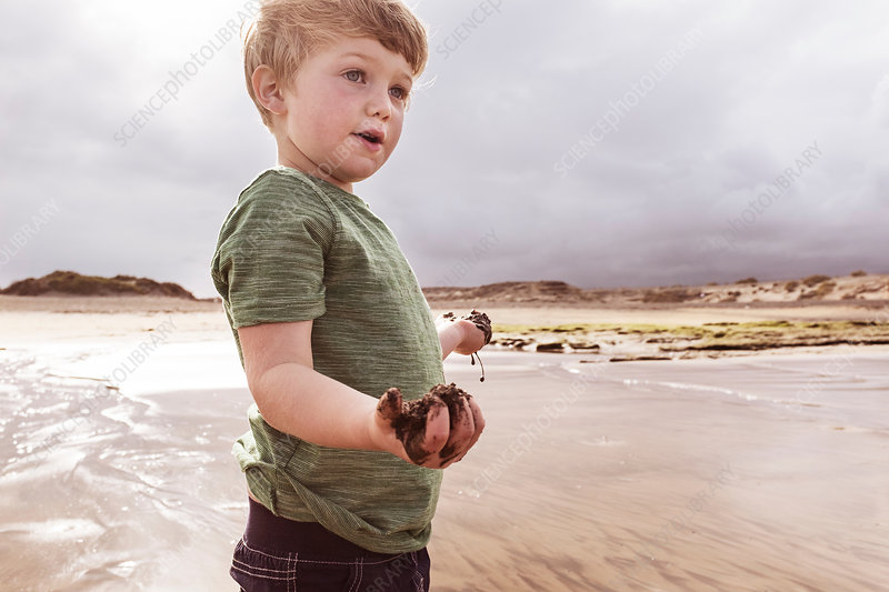 Young boy on beach, holding wet sand, Canary Islands, Spain