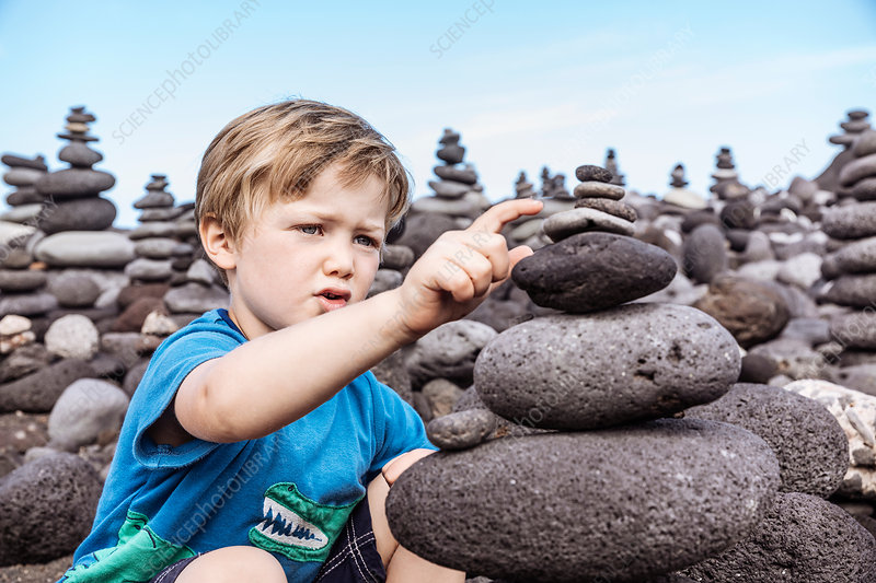 Young boy examining stack of rocks, Canary Islands, Spain