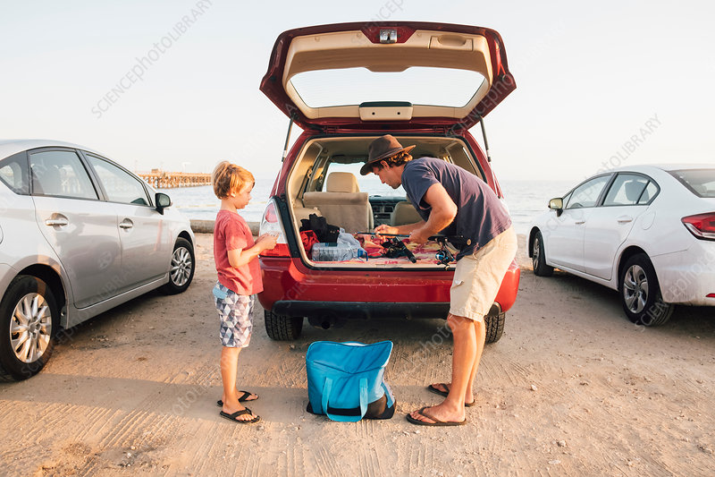 Father and son taking fishing rods from car boot, USA