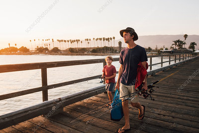 Father and son on pier with fishing rods, USA