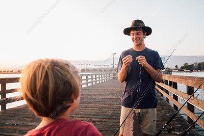 Father and son on pier preparing fishing rods, USA