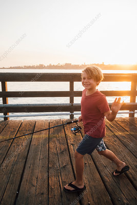 Boy on pier with fishing rod waving at camera smiling, USA
