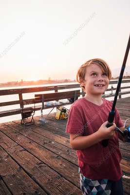 Boy on pier with fishing rod smiling, USA